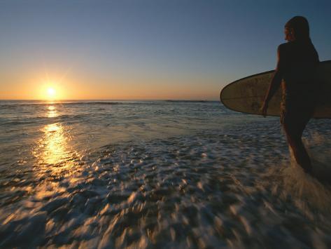 Donne che entra nelloceano con una tavola da surf sotto il braccio ...