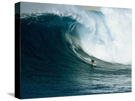 Ein Wellenreiter reitet auf einer mächtigen Welle vor der Nordküste von Maui Bedruckte aufgespannte Leinwand