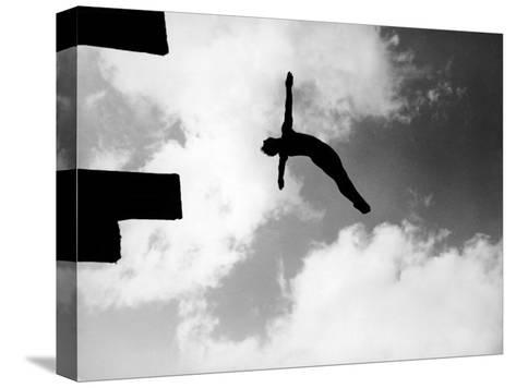 Excellent of Man Silhouetted Against Sky Doing Back Dive Off High Board Bedruckte aufgespannte Leinwand