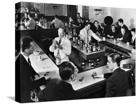 Bartender Prepares a Drink as Patrons Enjoy Themselves at Popular Speakeasy during Prohibition Stretched Canvas Print