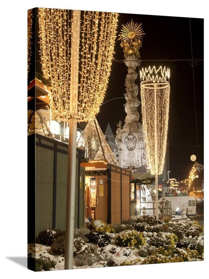 snow covered flowers christmas decorations and baroque trinity column at christmas market austria photographic print by richard nebesky at allposterscom