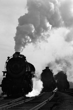 1930s-1940s Head-On View of Three Steam Engines Silhouetted Against Billowing Smoke and Steam