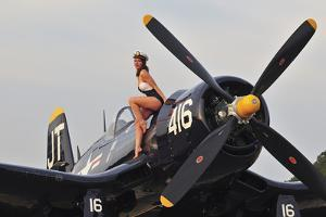 1940's Style Navy Pin-Up Girl Sitting on a Vintage Corsair Fighter Plane