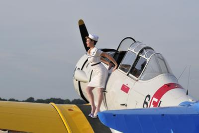 1940's Style Pin-Up Girl Sitting on the Wing of a Vintage T-6 Texan Aircraft