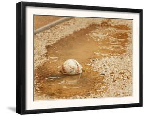 A Baseball Sits in a Puddle