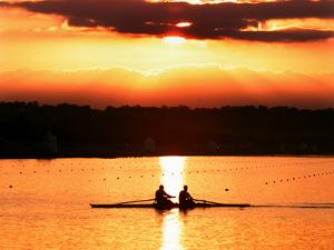 A Beautiful Sunrise Over the Sydney International Regatta Center Sillouhettes a Boat