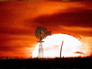 A Blazing Sun Drops Behind a Windmill