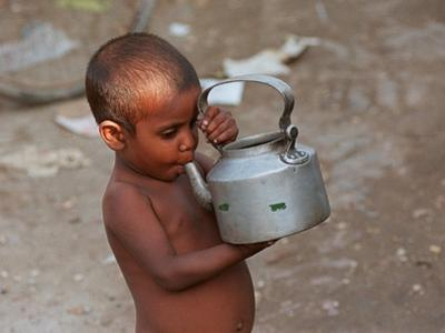 A Boy in a Slum Along the Yamuna River in the Older Part of New Delhi Drinks Water from a Tea Pot