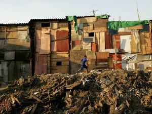 A Child Runs by a Row of Shacks in Novo Mundo Shantytown, Sao Paulo, Brazil