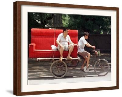 A Chinese Man Rides on a Sofa as Another Pedals a Delivery Tricycle