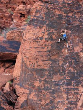 A Climber Ascends a Rock Face