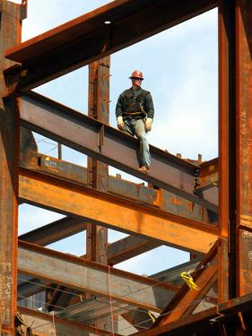A Construction Worker Stands on a Steel Beam While Working on a High Rise Building