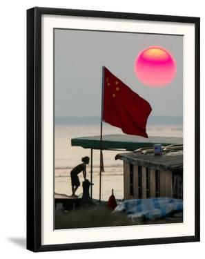 A Girl Rests on a Boat Below the Chinese National Flag