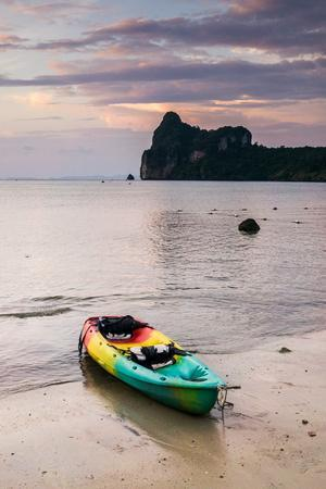 https://imgc.allpostersimages.com/img/posters/a-kayak-on-the-shore-of-phi-phi-island-at-sunset_u-L-Q1BBC5E0.jpg?p=0