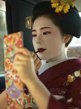 A Kimono-Clad Geisha Applies Lipstick in the Back of a Cab