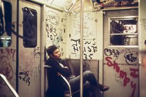 A Lone Passenger Amidst a Graffiti Painted Subway Car Interior, May 1973