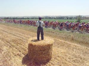 A Lone Spectator Watches the Pack Ride by from the Top of a Bale of Hay