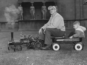 A Man and Young Boy Ride in a Wagon Being Pulled by a Model 'Case' Locomotive