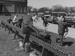 A Man Demonstrating a Steam Locomotive to a Group of Children