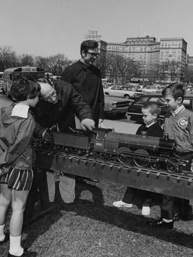 A Man Explaining a Steam Locomotive to a Group of Children