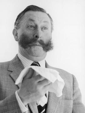 A Man with a Magnificent Moustache About to Sneeze into a Hanky