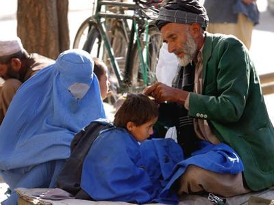 A Mother Watches as Her Child Gets a Haircut in the Center of Kabul, Afghanistan on Oct. 9, 2003.