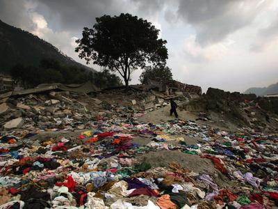 https://imgc.allpostersimages.com/img/posters/a-pakistani-refugee-walks-past-clothing-left-strewn-on-the-ground_u-L-Q10ORAM0.jpg?p=0