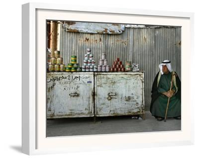 A Palestinian Sits Near the Stand of a Street Seller Displaying Goods for Sale