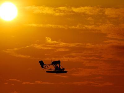https://imgc.allpostersimages.com/img/posters/a-pilot-flies-a-small-plane-past-the-setting-sun-over-lake-winnipesaukee_u-L-Q10ORSN0.jpg?p=0