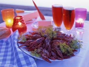 A Plate Full of Crayfish, Glasses with Beer and Lit Candles
