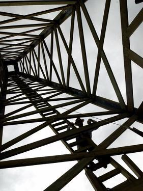 A Reenactor is Silhouetted Inside a Replica of the Spindletop Oil Derrick