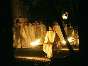 A Shinto Priest Walks, Holding a Wooden Torch, During the Tsukinami-Sai Ritual