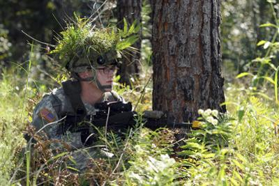 A Soldier Takes Cover Next to a Tree to Provide Security