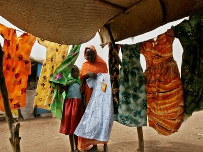 https://imgc.allpostersimages.com/img/posters/a-sudanese-woman-buys-a-dress-for-her-daughter-at-the-zamzam-refugee-camp_u-L-Q10ORQT0.jpg?p=0