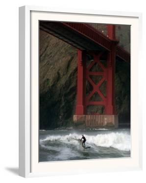 A Surfer is Dwarfed by the Northern End of the Golden Gate Bridge While Riding the Waves