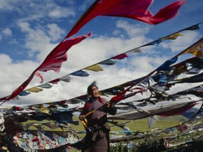 A Tibetan Pilgrim Hoists Prayer Flags Over a Mountain Pass in Tibet