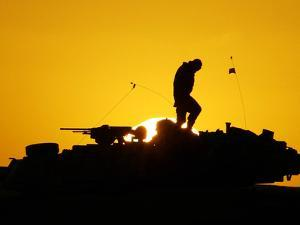 A U.S. Soldier Walks Atop His Armored Vehicle at Sunset