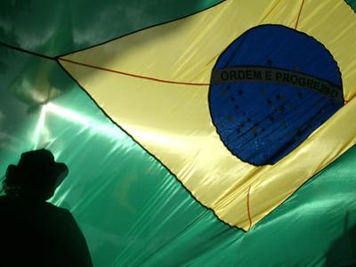 A Vendor Walks Behind a Big Brazilian Flag