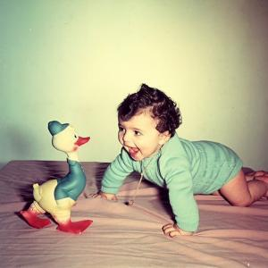 Baby Crawling Next to a Toy Duck by A. Villani