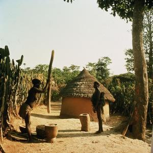 A Woman Grinding Millet with a Pestle and Mortar in a Miango Village Near Jos