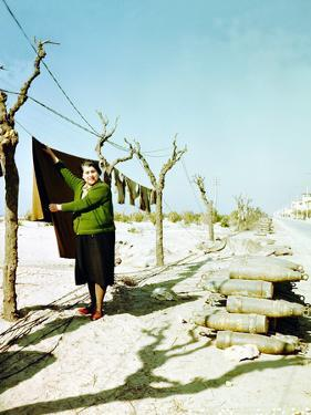 A Woman Hanging Her Laundry Right Next to 155mm Ammunition for the 92nd Infantry Division of the US