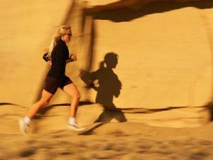 A Woman Jogs on a Mountain Path