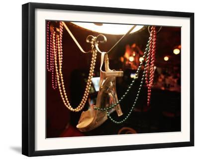 A Woman's High Heeled Shoe Hangs with Some Mardi Gras Beads