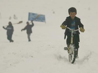 A Young Afghan Boy Rides His Bicycle on a Snow Covered Street