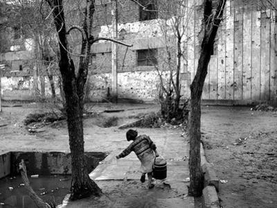 A Young Afghan Girl Carries Water from a Well to Her Family