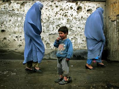 A Young Afghan Refugee Boy Stands in a Pair of Adult's Shoes