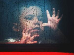 A Young Indonesian Boy Chases Raindrops on the Back Window of a Passenger Bus