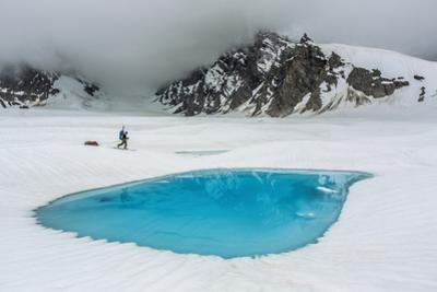 A climber skis past glacial pools atop upper Ruth Glacier in Denali National Park. by Aaron Huey