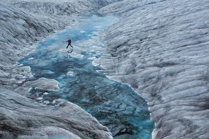 A Hiker Leaps across Ice Dotting a Glacial Pool by Aaron Huey
