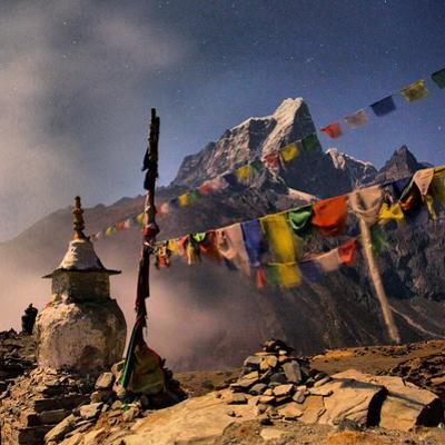 A Stupa and Prayer Flags Overlooking the Village of Dingboche with Taboche Peak in the Background by Aaron Huey